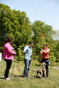 David works with Kelly and Chrislyn on the best way to set up a training exercise for a long-distance recall with Gunner. Hint: reward with tug toy.